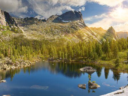 Summer morning over little lake. Sun rays shine between clouds. Ergaki Nature Park. Krasnoyarsk region Russia