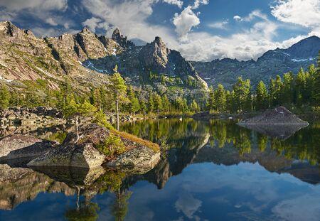 Matin d'été sur petit lac. Les rayons du soleil brillent entre les nuages. Parc naturel d'Ergaki. Région de Krasnoïarsk Russie