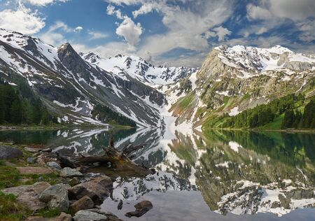 Upper Multinskoe mountain lake in the early morning. Mountains on a spring sunny day. Russia Siberia Mountain landscape with a forest in the foreground. Standard-Bild