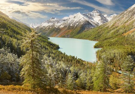 Mountain lake Russia West Siberia Altai mountains. Beautiful landscape sunny morning, mountain lake surrounded by autumnal pristine taiga forest after night snowfall. Standard-Bild