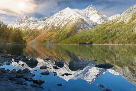 Bright sunny day. Mountain lake Russia West Siberia Mountain landscape with snowy white peaks and lake forest in the foreground. Mountains reflected in the lake.