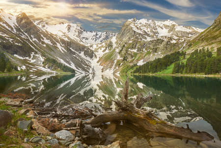Upper Multinskoe mountain lake in the early morning. Mountains on a spring sunny day. Russia Siberia Mountain landscape with a forest in the foreground. Standard-Bild - 155595852