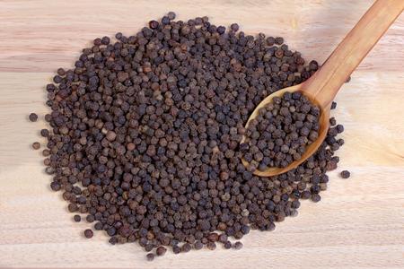 pepe nero: pepe nero su un cucchiaio di legno tavolo di legno. Archivio Fotografico
