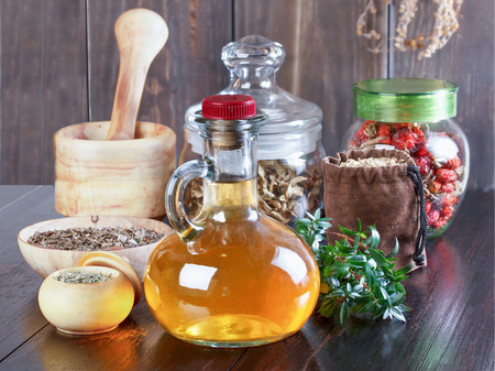 phial: Therapeutic herbal tincture, alternative medicine, love potions, dried herbs on a wooden table. Stock Photo