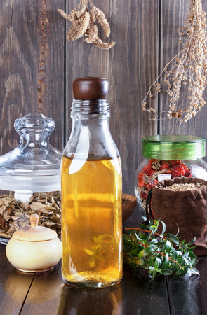 tincture: Therapeutic herbal tincture, alternative medicine, love potions, dried herbs on a wooden table. Stock Photo