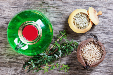 therapeutic: Therapeutic herbal tincture, alternative medicine, love potions, dried herbs on a wooden table. Stock Photo