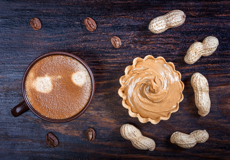 wooden basket: Espresso coffee in a ceramic bowl, basket waffle with peanut butter, peanuts, coffee beans on a wooden table.