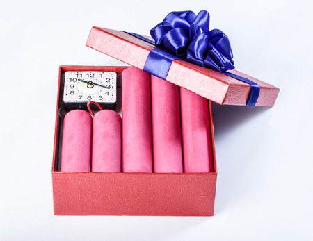 detonating: Bomb sticks of dynamite, in a gift box with a blue ribbon with clockwork, terrorism, closeup. Stock Photo