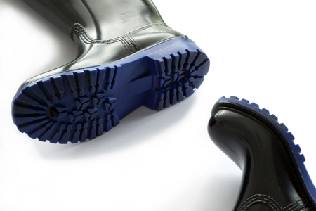 gumboots: Black rubber boots blue outsole on white background