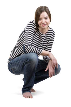 Girl brunette sitting barefoot in a striped shirt and blue jeans on a white background.