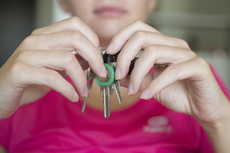 his: The girl with the door keys in his hands.
