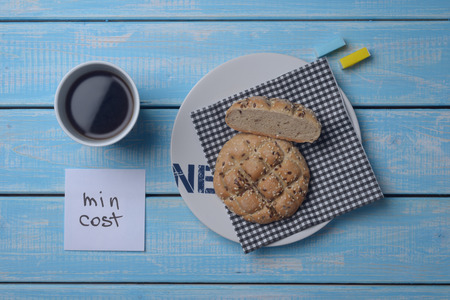 inexpensive: Inexpensive bun, a cup of coffee and two slices of sugar on a blue wooden table. The minimum cost.