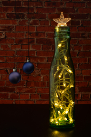 xmas background: Christmas tree with a star and a garland as a green bottle on the background wall of red brick. Stock Photo