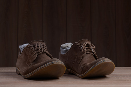 brogues: Brown suede shoes with brown laces and grey socks on the background of dark natural wood.