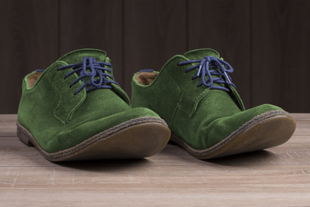 Green suede shoes with blue laces on the background of dark natural wood. Stock Photo
