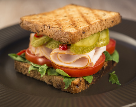 Sandwich with tomatoes, ham salted cucumber on a brown plate.