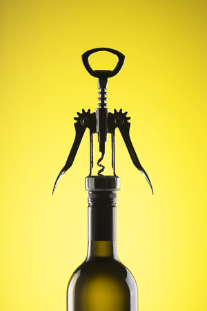 A bottle of wine with a stylish corkscrew for opening on a yellow background. Imagens