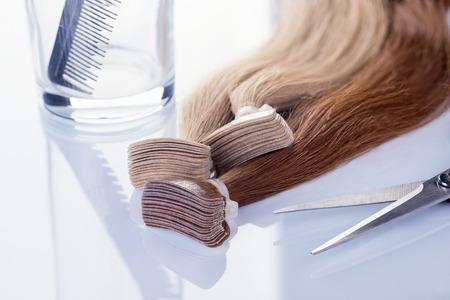 Cabello postizo coloreado con peine y tijeras. Cabello para la extensión del cabello sobre fondo blanco.
