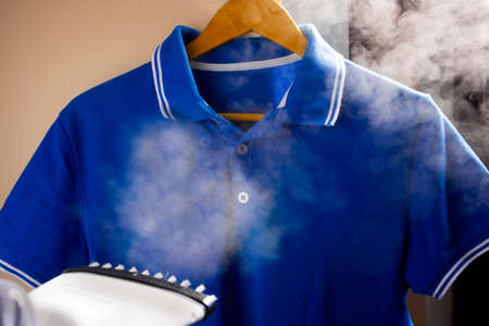 Ironing and steaming clothes with an iron. Pants and tennis shirt. Reklamní fotografie
