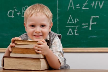 テーブルに座っている陽気な笑みを浮かべて男の子カメラ学校概念を見て