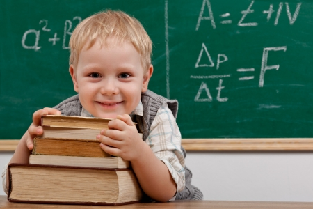 Cheerful smiling  little boy sitting at the table  Looking at camera School concept Standard-Bild