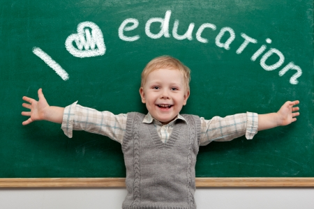 preschool children: Cheerful smiling child at the blackboard  School concept