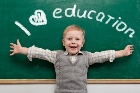ni�os en la escuela: Ni�o alegre que sonr�e en la pizarra de la escuela concepto
