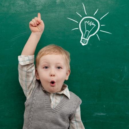 niños leyendo: Niño alegre que sonríe en la pizarra de la escuela concepto