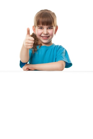 Portrait of a  smiling little girl   leaning on blank board with thumbs up against white background  Lots of copyspace for your text and logo  Advertising concept  Isolated on white photo