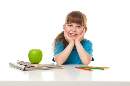 Retrato de uma menina sorridente sentado no conceito Escola tabela isolada no branco