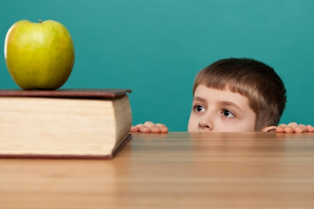 cheerful  little boy sitting at the table and looks at apple  School concept