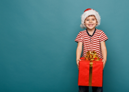 Smiling  funny child in Santa red hat holding Christmas gift in hand. Christmas concept. photo