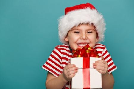 クリスマスのギフトを手で押し赤サンタ帽子で面白い子供の笑みを浮かべてください。クリスマスの概念。