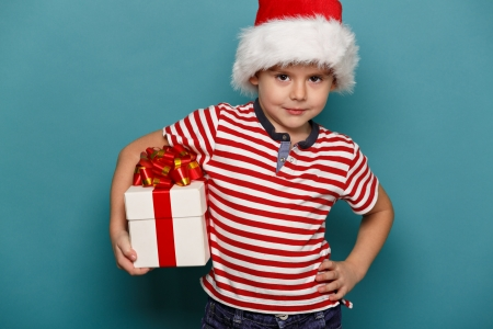 enjoy space: Smiling  funny child in Santa red hat holding Christmas gift in hand. Christmas concept.