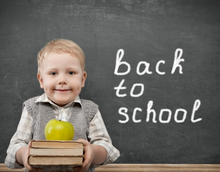 Cheerful smiling child with a book and apples stands at the blackboard. Looking at camera. School concept photo