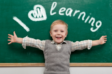 黒板に陽気な笑顔の子。学校概念