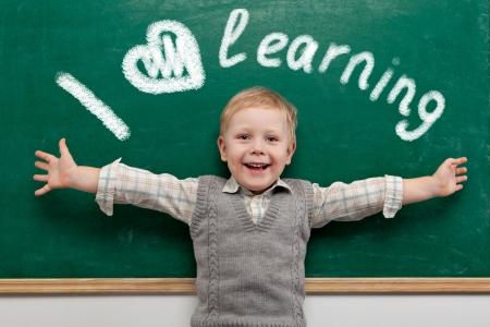 preescolar: Alegre sonriente ni�o en la pizarra. Escuela concepto