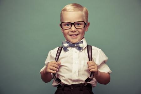 noeud papillon: Enthousiaste sourire drôle de garçon sur un fond vert.
