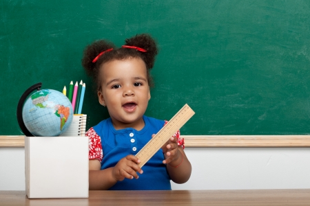 Cheerful smiling child  girl  at the blackboard  School concept