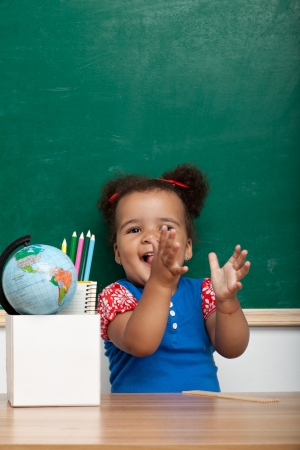 Cheerful smiling child  girl  at the blackboard  School concept photo