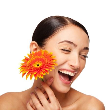 花と笑顔の美しい若い女性の肖像画。スタジオで取られます。