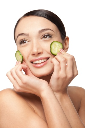 Close-up face of beautiful woman with clean fresh healthy skin and with cucumber slices around the cheeks. Isolated on white Stock Photo - 17344966