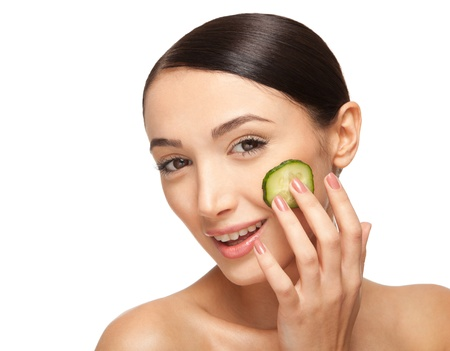 Close-up face of beautiful woman with clean fresh healthy skin and with cucumber slices around the cheeks. Isolated on white Stock Photo - 17344935