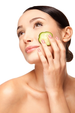 Close-up face of beautiful woman with clean fresh healthy skin and with cucumber slices around the cheeks. Isolated on white photo