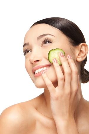 Face do Close-up da mulher bonita com a pele limpa e saudável com fatias de pepino ao redor das bochechas. Isolado no branco