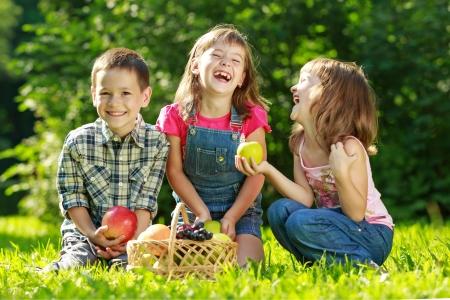 3 つの幸せな笑顔子供緑の芝生の公園で遊んでいると果物を食べる