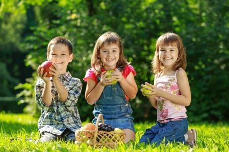 Três crianças sorrindo felizes brincando no parque na grama verde e comer frutas