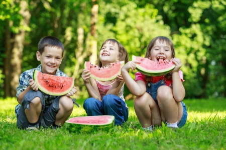 family picnic: Three happy smiling child playing in park on green grass and eating fruits