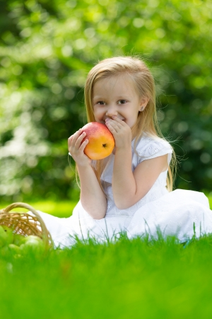 Happy smiling child sitting on green grass in park and eating apple photo