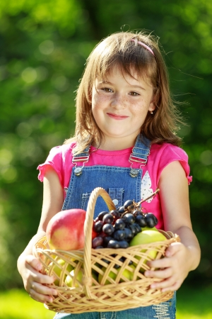 Happy smiling child (girl) playing in park on green grass and holding a basket of fruit photo